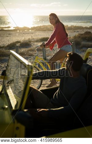 Happy caucasian couple on beach during sunset, woman riding bicycle, man sitting in beach buggy. beach break on summer holiday road trip.