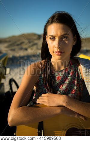 Portrait of happy caucasian woman on the beach holding guitar looking to camera. break on summer holiday road trip.