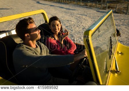 Caucasian couple sitting in beach buggy by the sea during sunset talking by phone. beach break on summer holiday road trip.