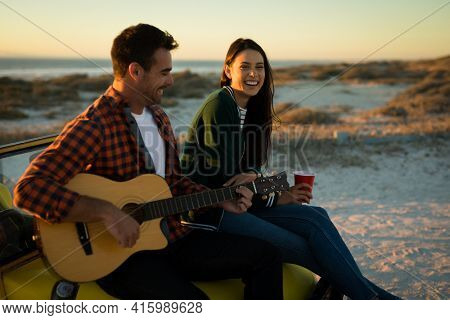 Happy caucasian couple sitting on beach buggy by the sea playing guitar and drinking during sunset. beach break on summer holiday road trip.