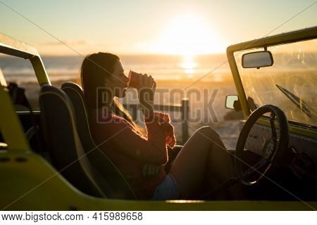 Caucasian woman sitting in beach buggy by the sea during sunset drinking. beach break on summer holiday road trip.