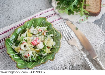 On The Table In A Ceramic Plate Vegetable Salad Of Cabbage, Pepper, Green Onions, Crab Sticks. Next