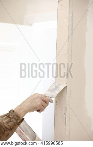 Builder Using A Trowel To Add Plaster. Plastering Wall With Putty-knife, Close Up Image. Fixing Wall