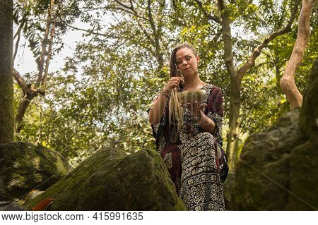 Caucasian Women With Dreadlocks With A Tibetan Bowl Among The Rocks. She Has A Piercing In Her Nose