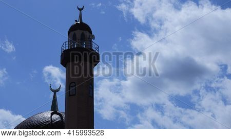 A Tower And A Dome Of A Mosque With An Islamic Crescent Against The Background Of A Shining White An