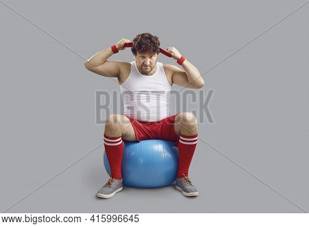 Funny Angry Chubby Man Sitting On Fitness Ball And Getting Ready For Gym Workout