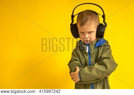 A Stern Kid In Wireless Headphones On A Yellow Background. The Child Does Not Like Music In Wireless