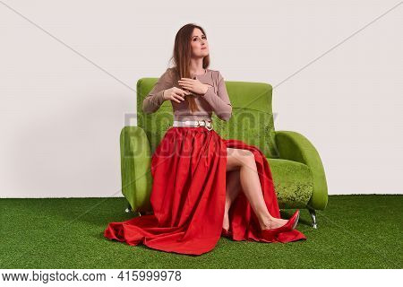 Young Beautiful Woman Combing Her Long Straight Hair With A Comb While Sitting On The Sofa In The St