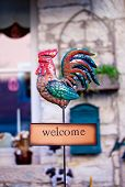 Photo of Welcome sign with iron rooster poster