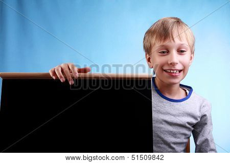 Beautiful cheerful blond boy in a blue t-shirt smiles happily presenting a small clean blackboard