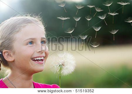 Summer joy - lovely girl blowing dandelion