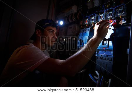 electrician worker detecting and fixing wire cabling damage breakdown with tester scredriver in power distribution fuseboard
