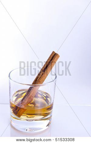 Tumbler With Brown Alcohol And Cinnimon Stick