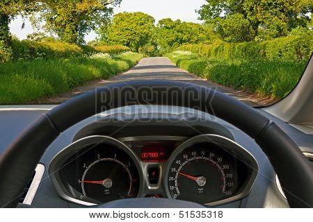 View from behind the steering wheel of a car whilst driving down a country road.