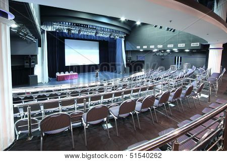 Document stand on stage and back of rows of chairs with handrails in big hall for business meetings.