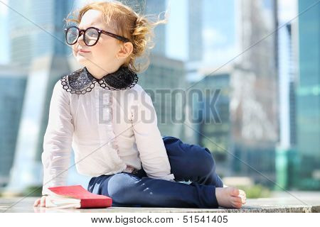 Little cute girl in glasses with red book sits on border near skys?raper at sunny day.
