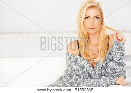 Sexy beautiful blond woman reclining on a white sofa in a stylish knitted top twiddling with her long hair and looking at the camera
