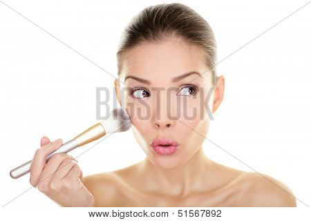 Makeup blush beauty woman looking funny away to side. Surprised cute adorable girl applying make-up on cheeks make up brush looking sideways. Mixed race Asian Chinese / Caucasian model, 20s, Isolated.