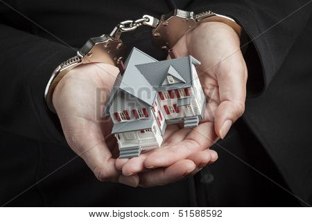 Woman In Handcuffs Holding Small House Against Black.