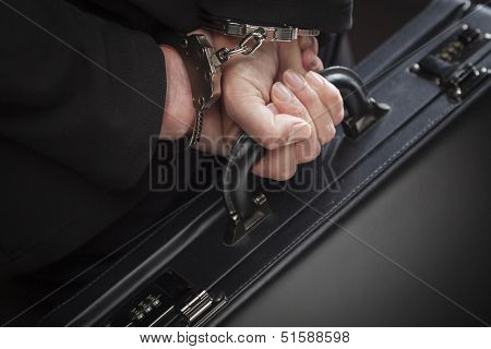 Woman Wearing Handcuffs Carrying Briefcase In Dramatic Lighting.