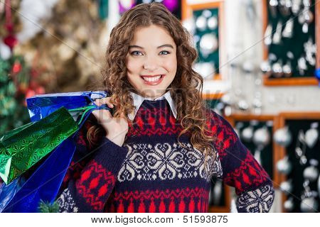 Portrait of happy young woman carrying shopping bags in Christmas store