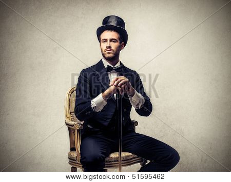 elegant man sitting on a chair with cylinder and vintage clothes
