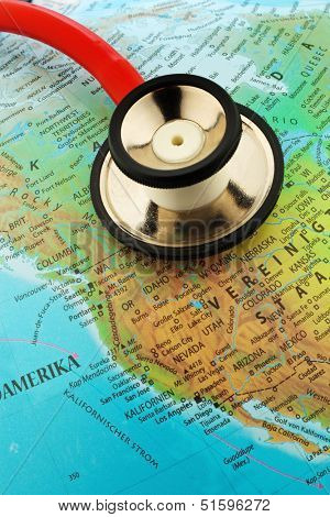 a stethoscope on a globe showing the americas.