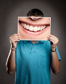 young man holding a picture of a mouth smiling poster
