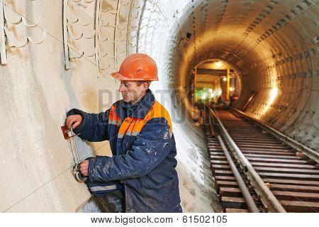Tuneller worker installing fixture in underground subway metro construction site