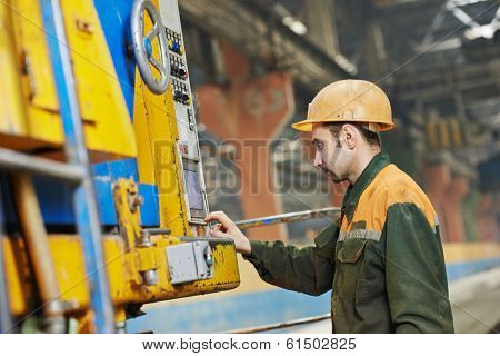 industrial worker operating concretemachine at factory workshop