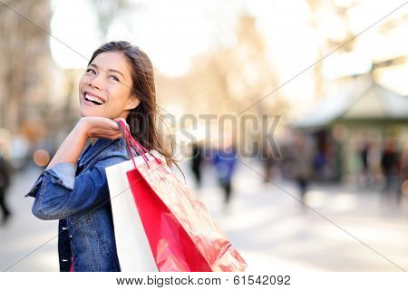 Shopping woman happy and looking away at copy space outdoors. Shopper girl holding shopping bags up excited outside on walking street. Mixed race Asian Caucasian female model on La Rambla, Barcelona. poster