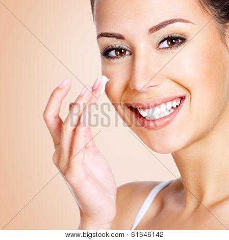 Smiling Woman Applying Cosmetic Cream