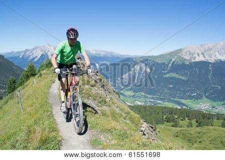 Mountain Biker Riding Downhill In Swiss Alps