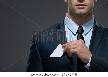 Part of body of man who pulls out business card from the pocket of business suit, copyspace