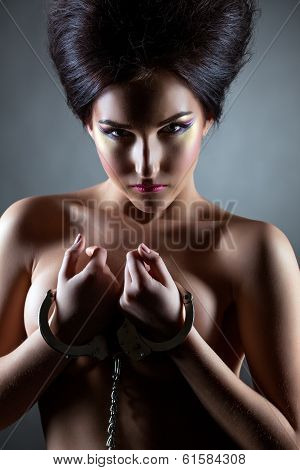 Shot of beautiful nude brunette posing handcuffed