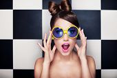 Attractive surprised young woman wearing sunglasses on checkered background, beauty and fashion concept poster