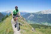 Mountain biker riding downhill in Swiss Alps in Graubünden region poster