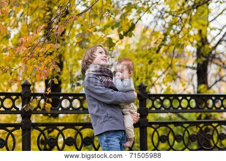 Brother And Baby Sister Walking In An Autumn City Park
