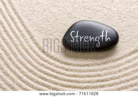 A black stone with the inscription Strength