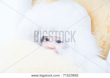 Baby Girl In A White Fur Jacket Sitting In A Stroller With A Warm Sheepskin Foot Muff
