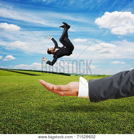 big palm catching small scared businessman over green field and blue sky