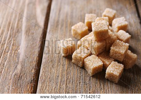 Brown sugar cubes on wooden background