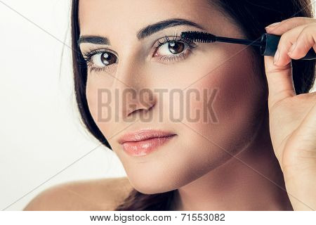 Woman applying mascara on her long eyelashes poster