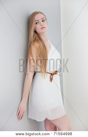Woman Wearing White Dress Leaning Against Wall
