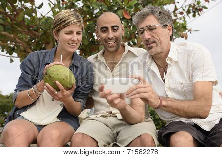 Middle aged group of friends looking at photo on phone