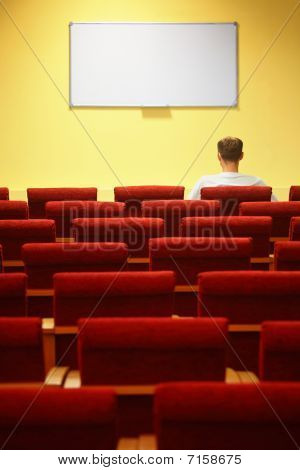 rows of a chairs. focus on a first row. one man sitting in chair