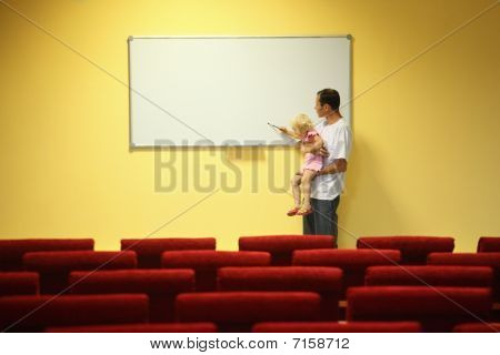 father and little girl in empty presentation hall.