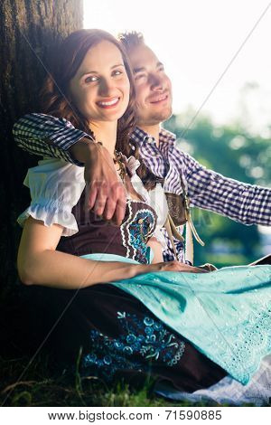 Bavarian couple in Tracht hugging under tree