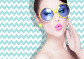 Attractive surprised young woman wearing sunglasses on zig zag background, beauty and fashion concept  poster