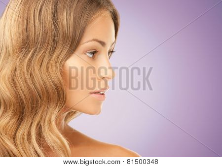 beauty, people and health concept - beautiful young woman face over violet background